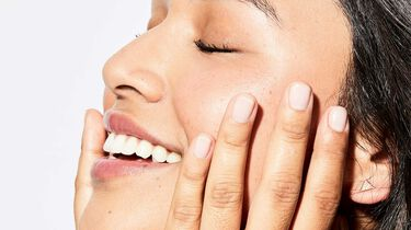 model touching her face with a smile