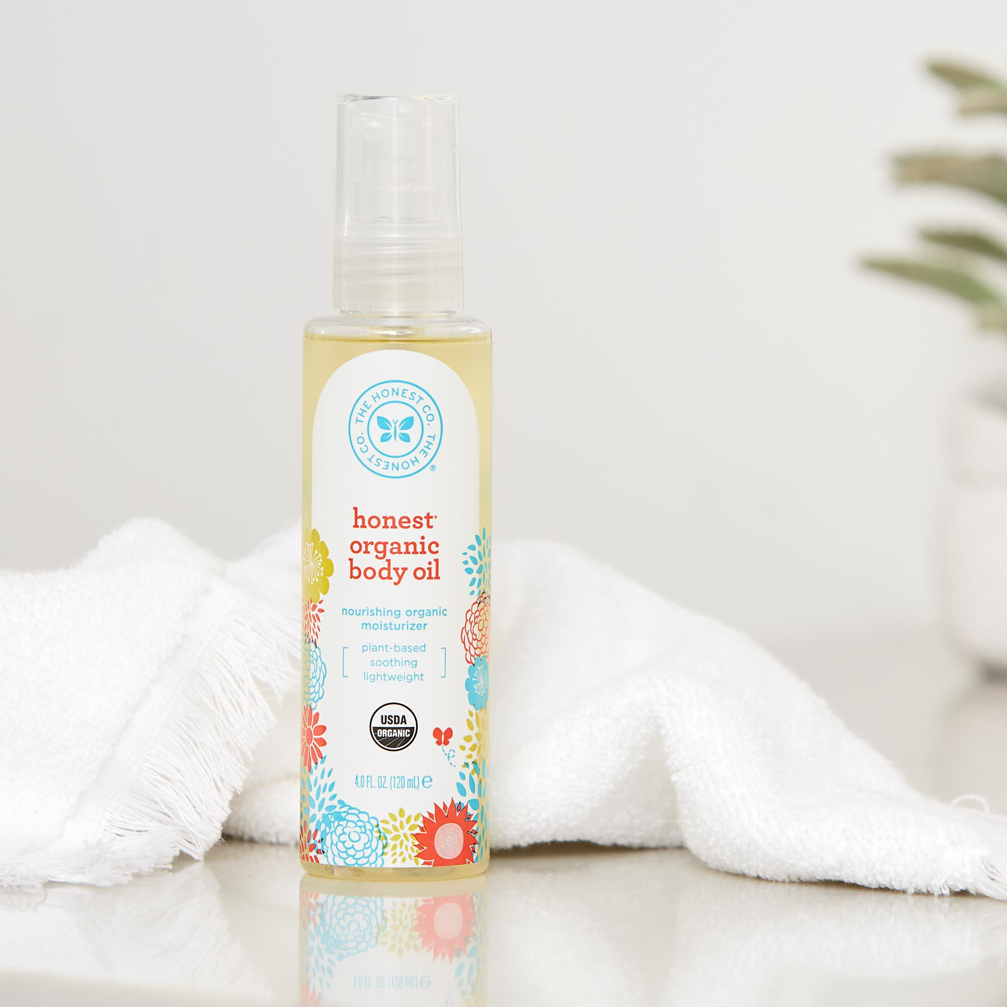honest organic body oil in bath setting with towel