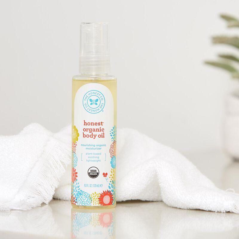 honest organic body oil in bath setting with towel