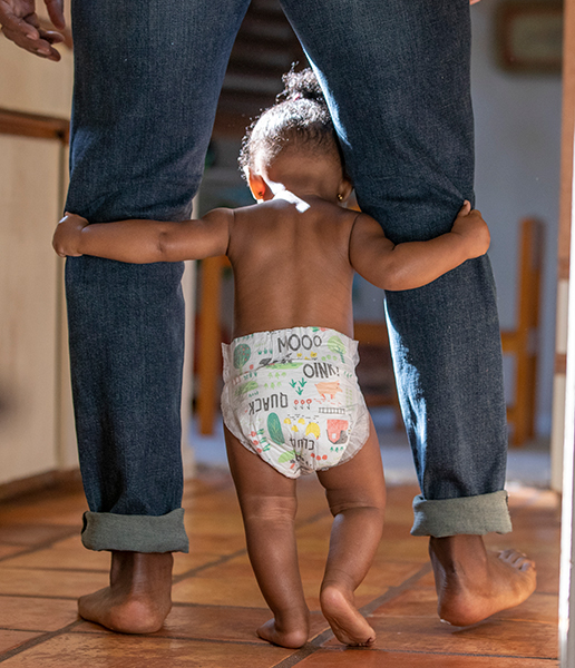 Baby walking in between dad's legs