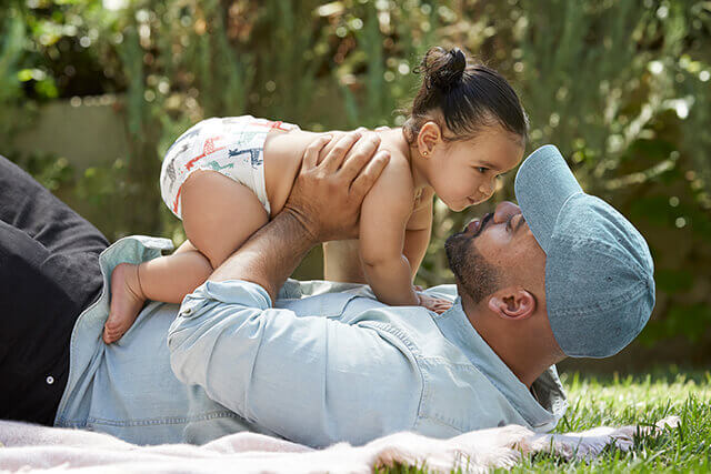 Father playing with baby girl in grass