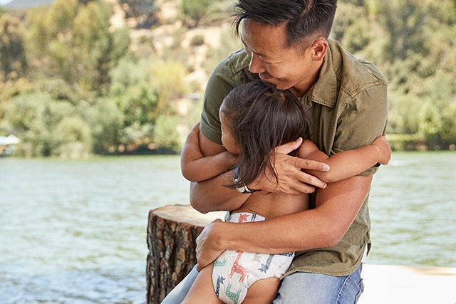 Dad hugs baby girl at the lake