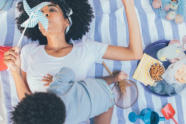 Mother blowing on a pinwheel while laying on a blanket with her baby boy