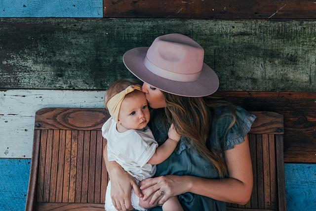 Mother kissing her baby girl on the head