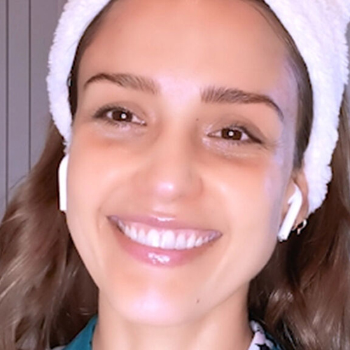 Jessica Alba smiling with earbuds