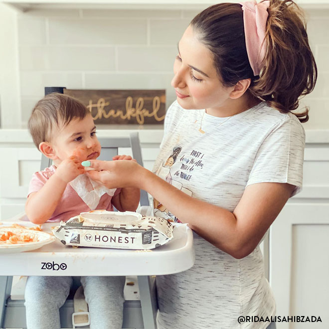Mom using honest wipes with baby