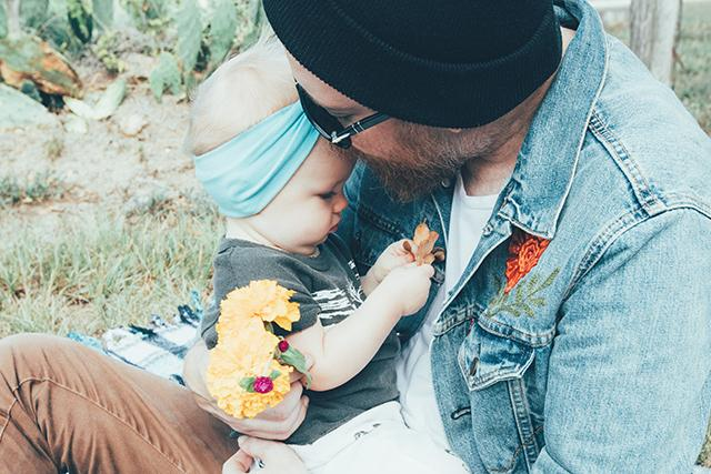 Father holding his baby girl while she plays with a flower