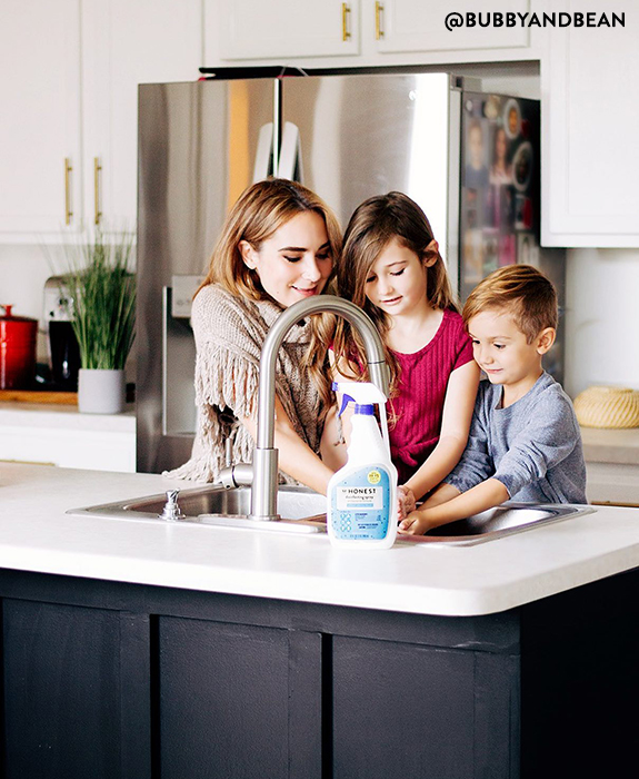Family washing hands next to honest disinfecting spray